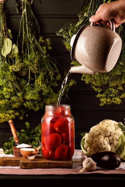 テーブルの上にはトマトの瓶、塩入れ、ニンニクがあります。やかんから、手が瓶に沸騰した水を注ぐ。ディルの束がそれらにかかっています。 Premium写真
