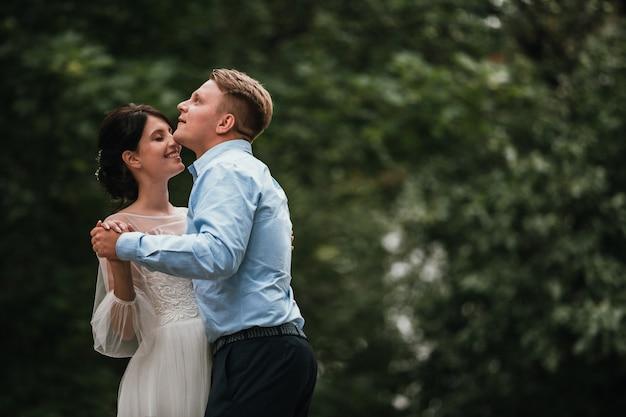 春の自然の屋外歩行の日の結婚式で新郎新婦。ブライダルカップル、幸せな新婚女と緑豊かな公園を受け入れる男。屋外の結婚式のカップルを愛しています。新郎新婦 Premium写真