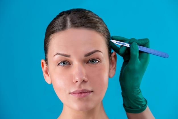 Портрет красивой девушки крупным планом, с гладкой кожей, руки держат скальпель в лицо в перчатках. концепция красоты, сохранение молодости, пластическая хирургия, здоровье. Premium Фотографии