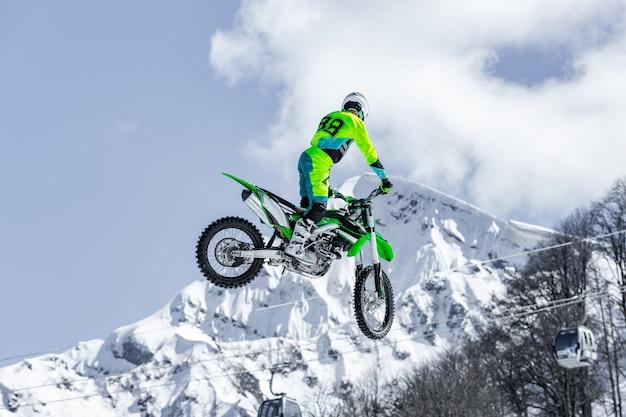飛行中のオートバイのレーサーは、雪に覆われた山を背景に飛び跳ねて飛び降りる Premium写真