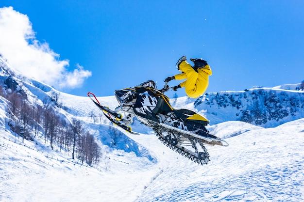 雪猫の飛行中のレーサーは、雪に覆われた山を背景に飛び跳ねて飛び降りる Premium写真