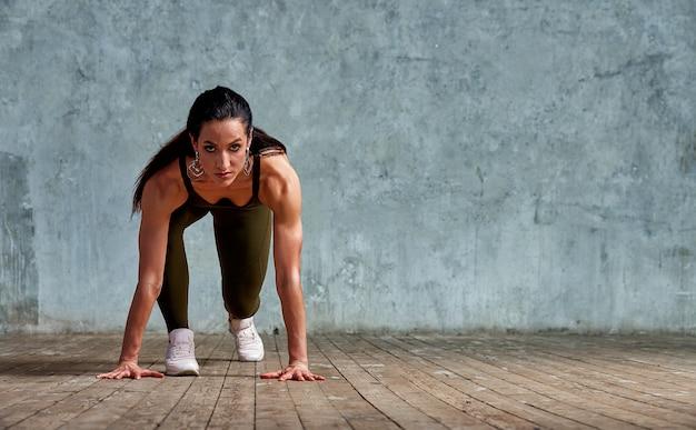 Фитнес-спортсмен на старте у стены готовится к спринту Premium Фотографии