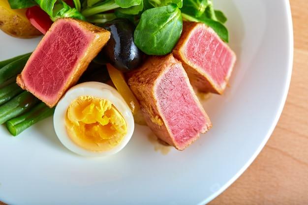 ツナのグリルと木製の背景にゆで卵のニース風サラダ Premium写真