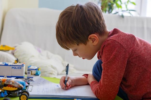 小さな男の子は宿題をしています Premium写真