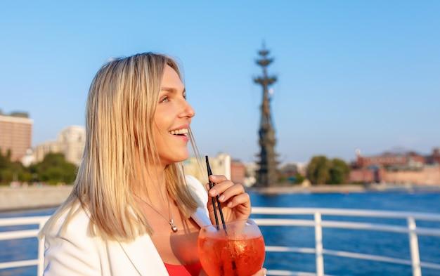 クルーズ船のデッキで景色を楽しみながら若いきれいな女性 Premium写真