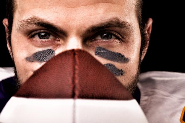 アメリカンフットボール選手のボールを保持していると見ているの肖像画 Premium写真