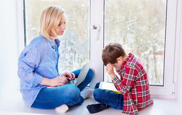 母と息子のガジェットと窓辺に座って Premium写真