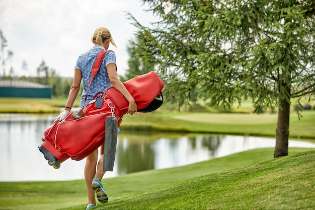 緑の野原でゴルフ用品を保持しているゴルフプレーヤー Premium写真