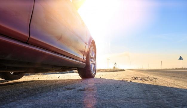 Закройте вверх перед новый красный автомобиль на асфальтированной дороге в солнечный день Premium Фотографии