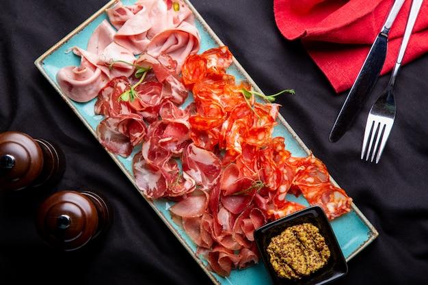 冷たい肉の盛り合わせ、生ハム、スライスハム、ビーフジャーキー、サラミ、肉とマスタード Premium写真