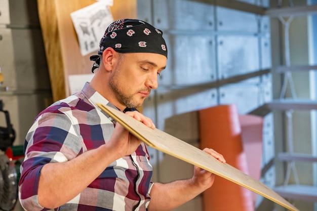 Плотник делает свою работу в столярной мастерской. человек в столярной мастерской измеряет и режет ламинат Premium Фотографии