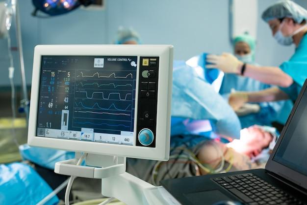 Электрокардиограмма в отделении скорой помощи, показывающая частоту сердечных сокращений пациента с командой размытия хирургов Premium Фотографии