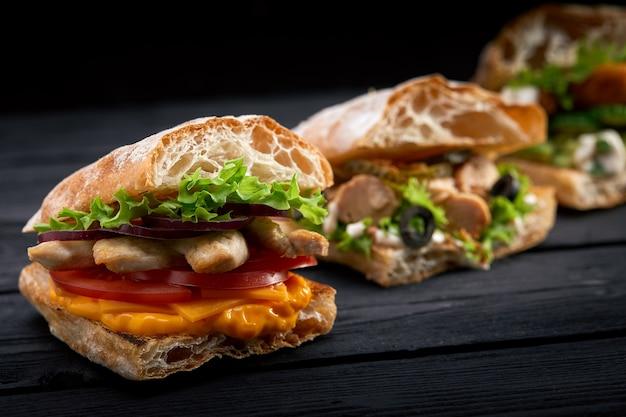 Крупным планом три разные аппетитные бутерброды или гамбургеры на деревянном фоне Premium Фотографии