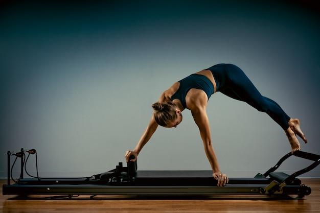 Молодая девушка делает упражнения пилатес с кроватью реформатора. красивый тонкий фитнес-тренер на фоне реформатора серый, низкий ключ, свет искусства. концепция фитнеса Premium Фотографии