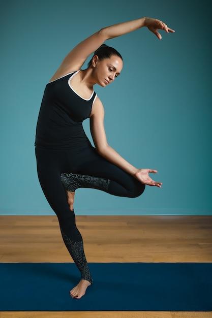 立っているストレッチを行うスポーティな若い女性。青の背景に屋内でヨガを練習するスリムな女の子。落ち着いて、リラックスして、健康的なライフスタイルのコンセプト。 Premium写真