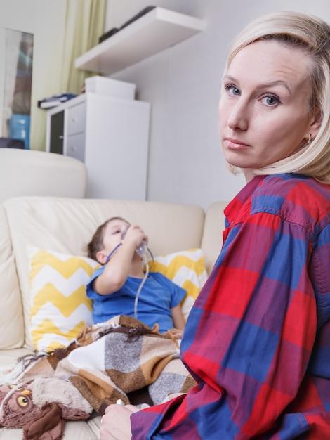 病気の子供と母親。小児ネブライザーで病気の子供。喘息や気管支炎の小さな子供は呼吸困難です。 Premium写真