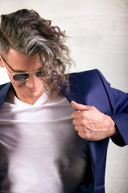 Молодой бизнесмен надевая его куртка изолированная над белизной. Premium Фотографии