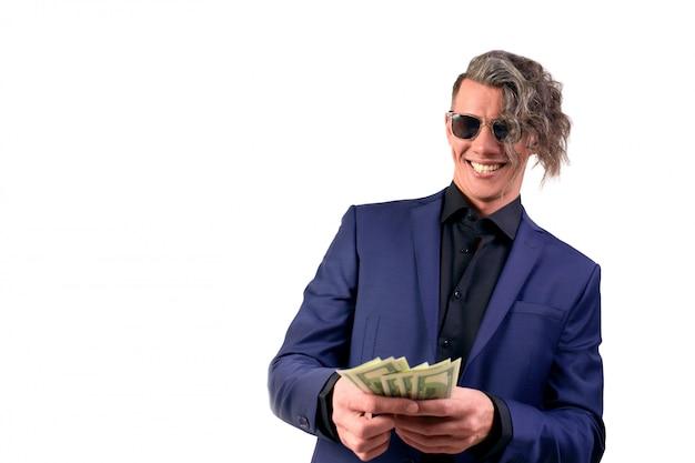 白い背景にお金を投げる実業家。スーツを着た男は、お金を無駄にし、紙幣、ドルを投げます。 Premium写真