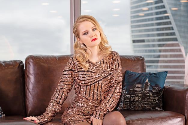 若い美しいブロンドの女性は、高層ビルと大都市を見下ろすパノラマウィンドウの背景に革張りのソファに座っています。 Premium写真