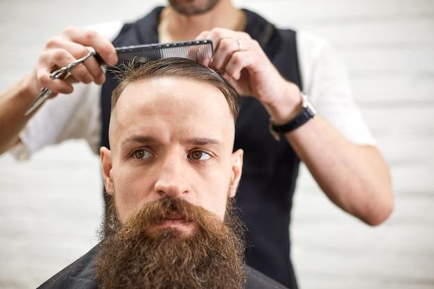 Брутальный парень в современной парикмахерской. парикмахер делает прическу мужчине с длинной бородой. мастер-парикмахер делает прическу с помощью машинки для стрижки волос Premium Фотографии