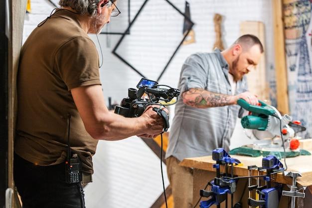 За кулисами производства для операторской съемки видеоаппаратуры, установленной сцены с работником Premium Фотографии