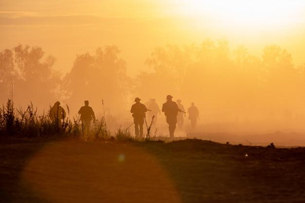シルエットアクション兵士が歩いて背景を保持する武器は煙と日没です。戦争、軍事および危険の概念 Premium写真