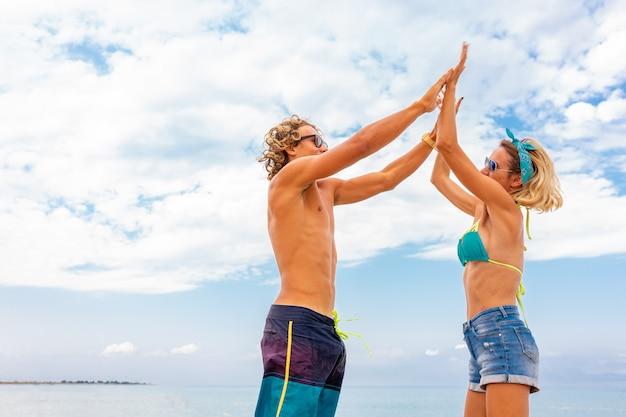 Портрет молодой пары в любви, охватывающей на пляже и наслаждаясь время быть вместе. молодая пара развлекается на песчаном берегу Premium Фотографии