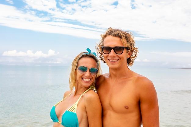 Портрет молодой пары в любви, охватывающей на пляже и наслаждаясь время быть вместе. идеалистическое художественное фото постер для рекламного баннера Premium Фотографии