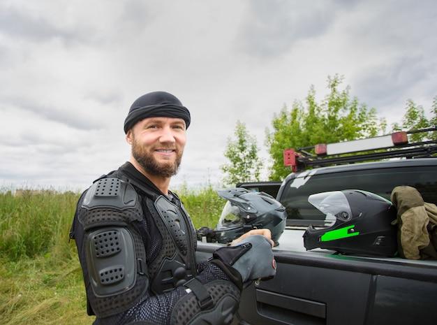 屋外オートバイのギアを着て幸せな笑みを浮かべて若い男。 Premium写真