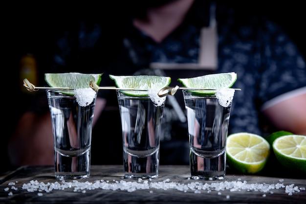 Аперитив с друзьями в баре, три бокала спирта с лаймом и солью для украшения. текила выстрелы, выборочный фокус Premium Фотографии