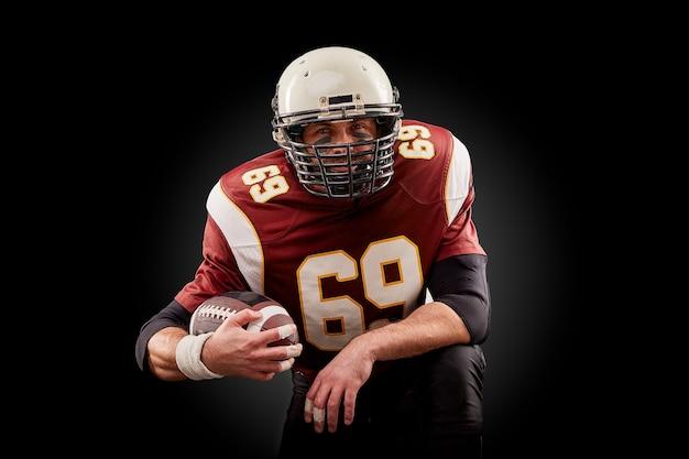 Портрет игрока американского футбола держа мяч обеими руками Premium Фотографии
