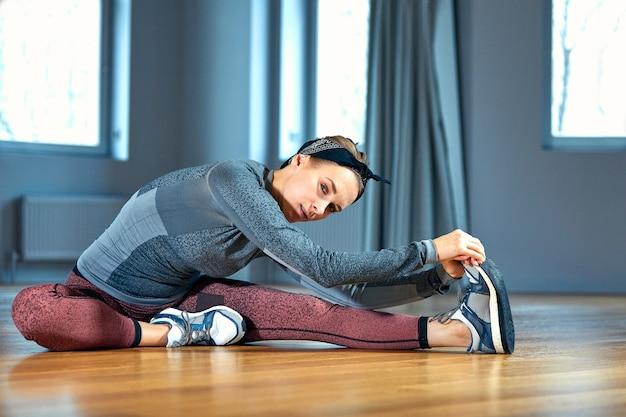 Молодая красивая женщина в спортивной одежде делает растяжку сидя на полу перед окном в тренажерном зале Premium Фотографии