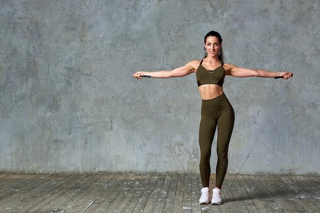 彼女の手、フィットネスの概念でジャンパーと灰色の壁に対して全身ジムでポーズをとって笑顔のフィットネスモデル Premium写真