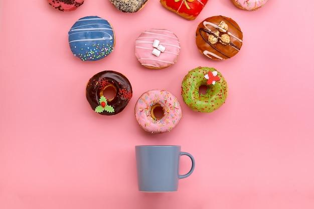 パステルカラーのバラの表面にアイシングとコーヒーカップとカラフルなドーナツ。甘いドーナツ。 Premium写真
