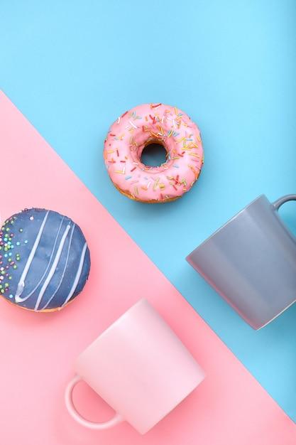 パステルブルーとローズの表面にアイシングとコーヒーカップのドーナツ、甘いドーナツ。 Premium写真