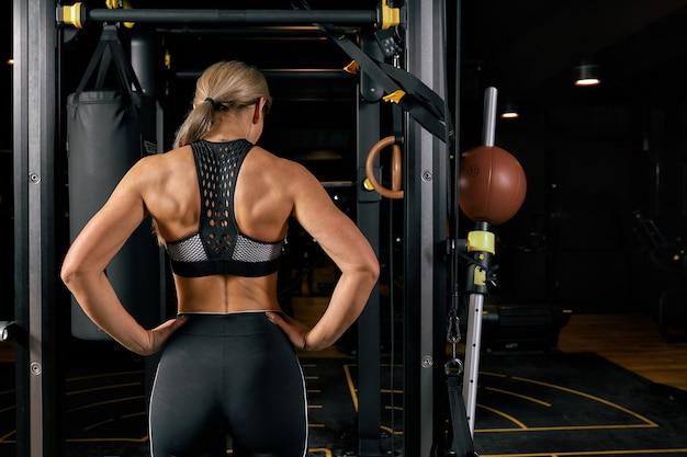 スポーツ、フィットネス、ライフスタイル、人々の概念。女性運動と後ろからジムでプルアップを行う Premium写真