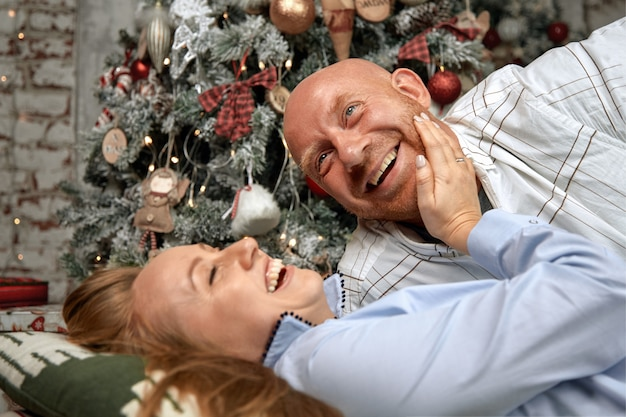 陽気なカップルを抱いて、クリスマスイブに一緒に楽しんで。奇跡、家族の結婚、新年の若いカップルを見越してクリスマスコンセプト。 Premium写真