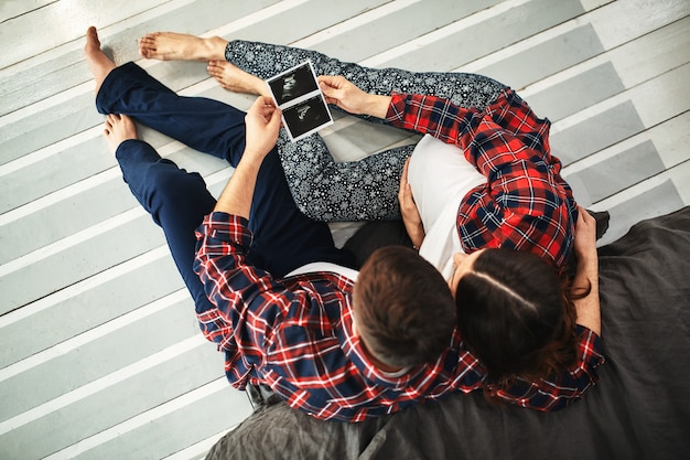 赤ちゃんを待っている若い夫婦。寝室に横たわっている美しいカップルは、赤ちゃんの誕生の計画を立てます。最初の子供、産後、若い家族。 Premium写真