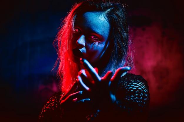 Женская модель в хэллоуин наряд позирует с на красный. великолепная девушка в одежде празднует день мертвых. хэллоуин концепция, костюм ведьмы, яркие цвета, пара панк. Premium Фотографии