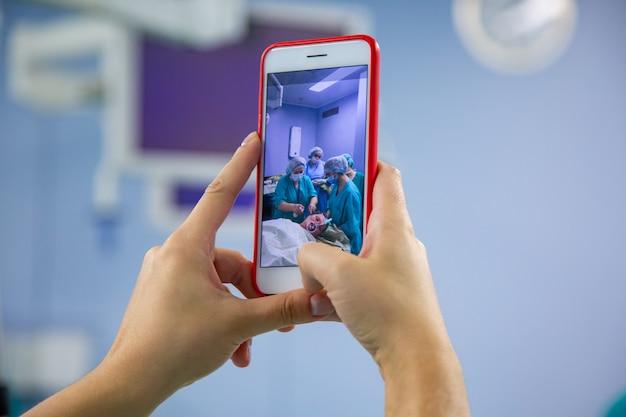 手術室からスマートフォンでのアシスタント撮影。現代の手術室で外科手術を行う医療チーム Premium写真