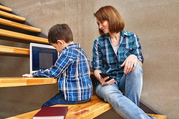 Мама и сын делают домашнее задание на компьютере Premium Фотографии