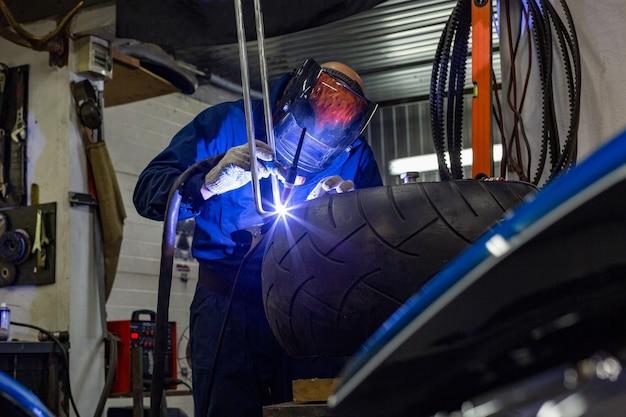 Профессиональный автомеханик, работающий в автосервисе на аргонорезной машине Premium Фотографии