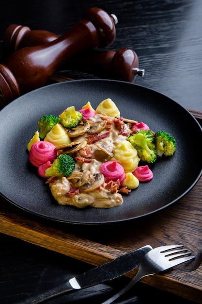 Вкусные блюда из говядины строганы ресторан блюдо в ресторане. здоровая эксклюзивная еда на большом черном блюде крупным планом Premium Фотографии