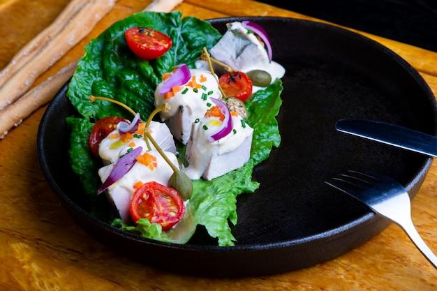 Вкусный ресторан блюдо вителло тонато в ресторане. здоровая эксклюзивная еда на большом черном блюде крупным планом Premium Фотографии