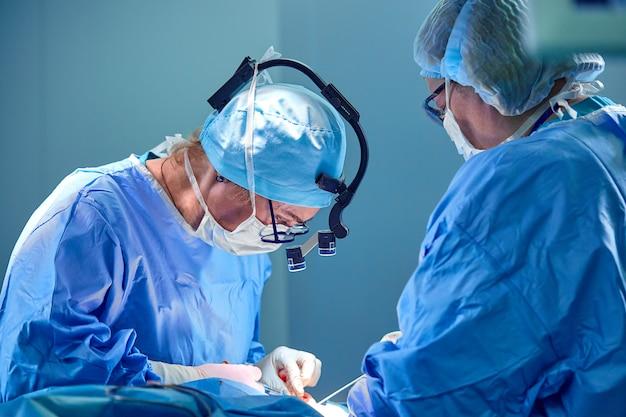 外科医と彼のアシスタントは病院の手術室で美容整形手術を行います。 Premium写真