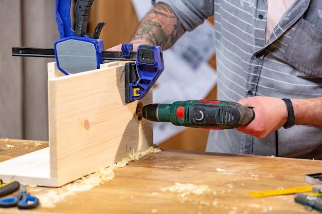 職業、大工、木工、人々のコンセプト-ワークショップで木の板を掘削電気ドリルを持つ大工 Premium写真