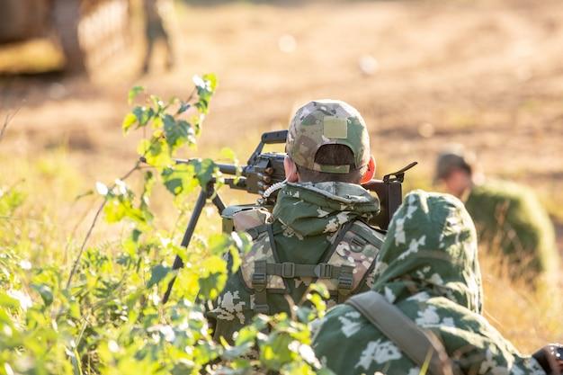 Снайперская бригада, вооруженная крупнокалиберной снайперской винтовкой, стреляет по вражеским целям на расстоянии от укрытия, сидит в засаде Premium Фотографии