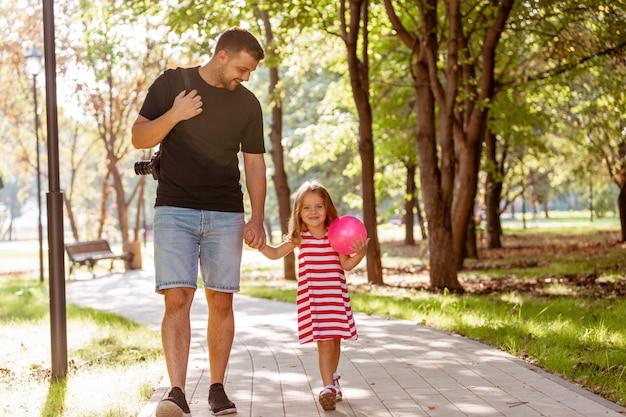Счастливый отец и маленькая девочка гуляют, держа в руке в парке летом Premium Фотографии
