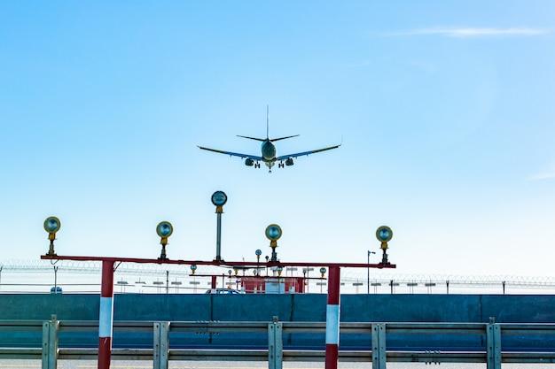 太陽光線で青い空を飛んでいる旅客機 Premium写真
