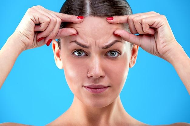 老化の兆候。ショックを受けた若い女性の肖像画は青い壁の額に彼女のしわに触れている間がっかりして探しています Premium写真